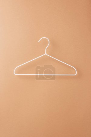 Photo for One empty white hanger on beige - Royalty Free Image