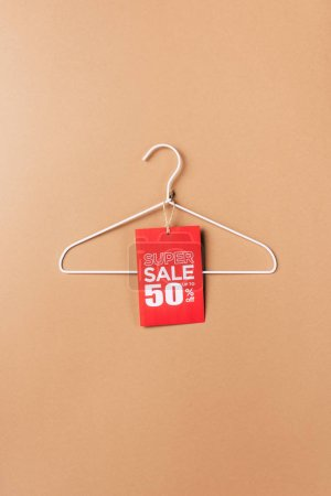 hanger with red super sale tag with fifty percents discount on beige