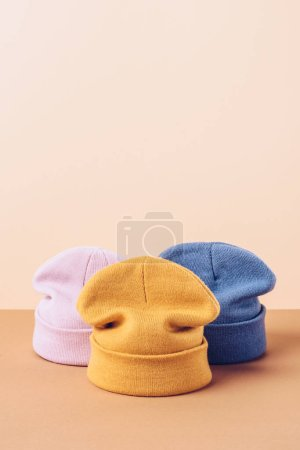three casual autumn hats on beige