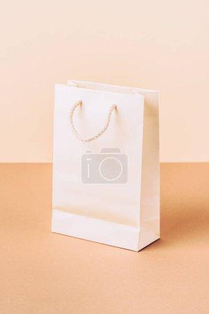 white paper shopping bag on beige