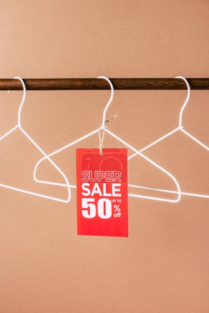 hangers with red super sale tag - 50 percents discount for black friday shopping on beige