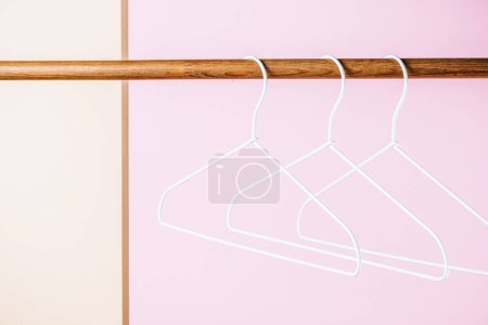 three white empty hangers for shopping on pink