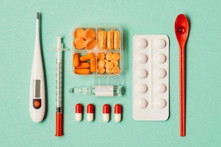 Photo pour Vue de dessus de divers médicaments, seringue et thermomètre sur vert - image libre de droit