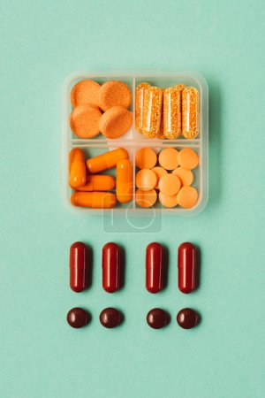 top view of drugs in container, medical pills and capsules isolated on green