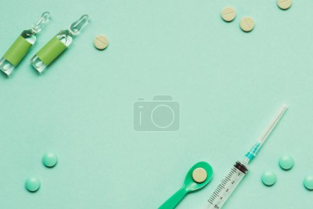 top view of ampoules with medicines, pills and syringe on green background