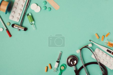 Photo for Top view of various medical pills and instruments on green background - Royalty Free Image