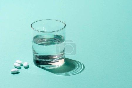 Photo pour Vue rapprochée du verre d'eau et pilules médicales sur vert - image libre de droit