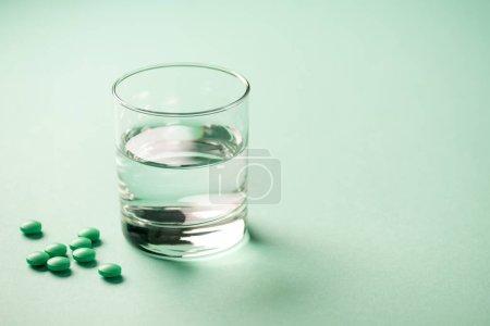 Photo pour Vue rapprochée du verre d'eau et des comprimés médicaux sur vert - image libre de droit