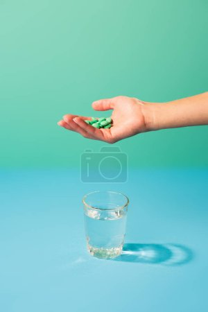 cropped shot of person holding pills above glass of water on green