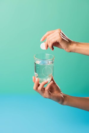 cropped shot of person holding glass of water and pill isolated on green