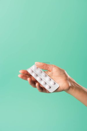 cropped shot of person holding blister pack with tablets isolated on green