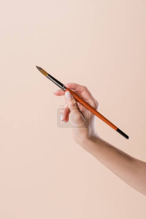 cropped shot of woman holding watercolor paint brush isolated on beige