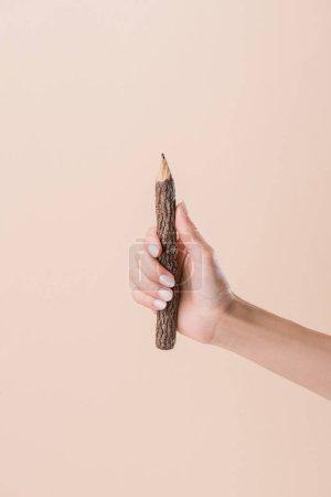 photo recadrée de femme tenant le crayon fait de bâton isolé sur beige