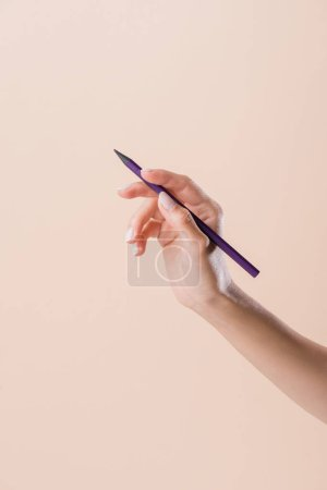 cropped shot of woman holding purple pencil isolated on beige