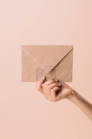 cropped shot of woman holding envelope isolated on beige