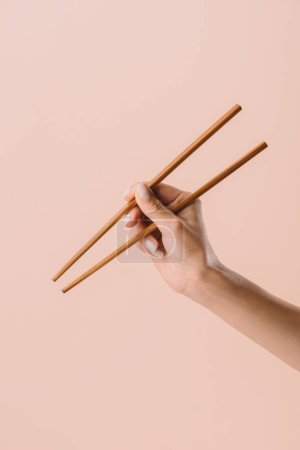 cropped shot of woman holding chopsticks isolated on beige