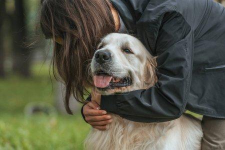 Photo pour Jeune femme étreignant mignon drôle chien dans le parc - image libre de droit