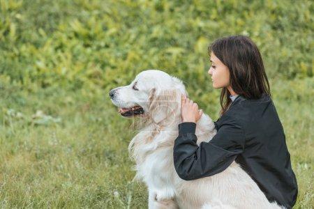 Foto de Hermosa joven abrazando a perro y sentados sobre la hierba en el Parque - Imagen libre de derechos