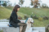 young woman working with laptop while sitting with dog in park