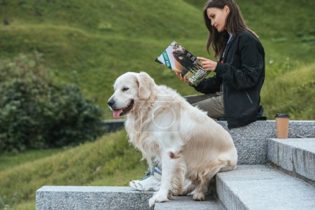 young woman reading magazine while sitting with dog in park