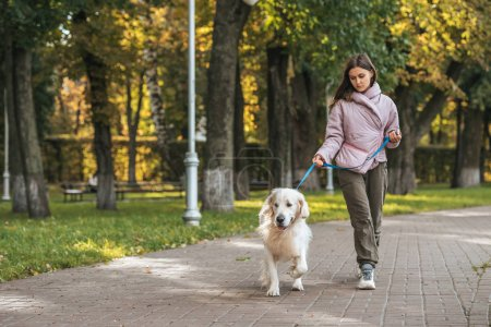 young woman walking with guide dog in park