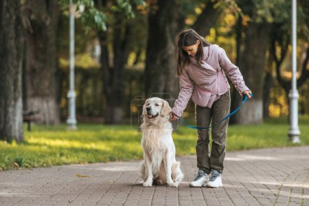 young woman holding leash while walking with dog in park