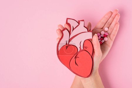Photo for Cropped image of woman holding anatomical human heart and various pills on pink - Royalty Free Image