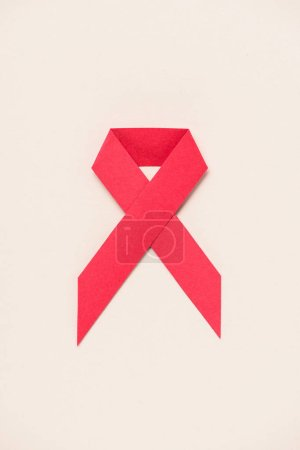 top view of HIV and AIDS awareness red ribbon on beige