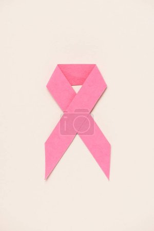 top view of breast cancer awareness pink ribbon on beige