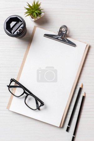 vue du dessus de tasse à café en papier, crayons, plante en pot et presse-papiers vide à la table dans le bureau