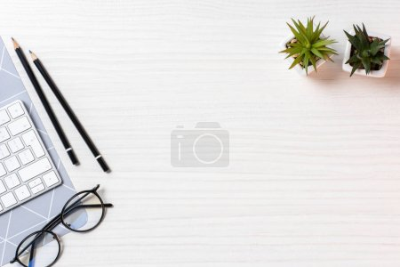 Photo for Elevated view of workplace with eyeglasses, plants and computer keyboard in office - Royalty Free Image