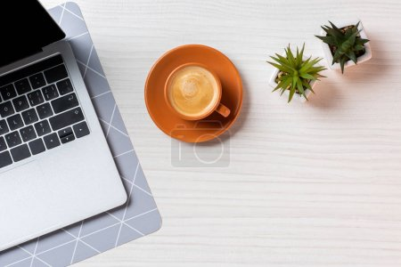 Photo for Flat lay with laptop, coffee cup and green potted plants at table in office - Royalty Free Image