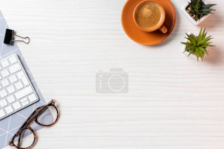 top view of coffee cup, eyeglasses, potted plants and computer keyboard at table in office