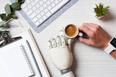 Photo for Cropped image of businessman with prosthesis hand and smartwatch sitting at table with coffee cup and computer keyboard in office - Royalty Free Image
