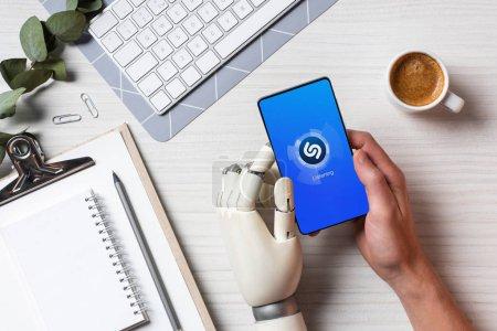 Foto de Recortar imagen de empresario con brazo de prótesis con smartphone con shazam en pantalla a la mesa con la taza de café en la oficina - Imagen libre de derechos