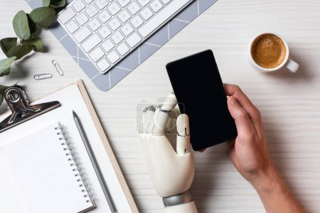 Photo for Cropped image of businessman with prosthesis arm using smartphone with blank screen at table with coffee cup in office - Royalty Free Image