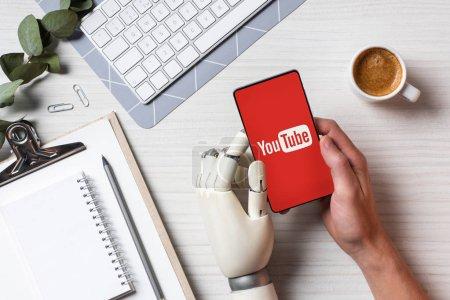 Foto de Vista parcial del empresario con el brazo de prótesis con smartphone youtube en pantalla a la mesa con la taza de café en la oficina - Imagen libre de derechos