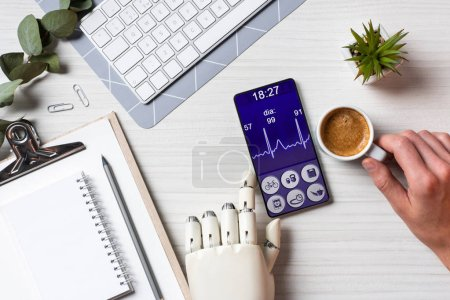 Photo for Partial view of businessman with prosthesis arm using smartphone with medical application on screen at table with coffee cup in office - Royalty Free Image