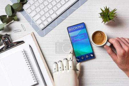 Photo for Partial view of businessman with prosthesis arm using smartphone with booking on screen at table with coffee cup in office - Royalty Free Image