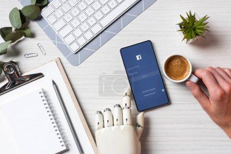 Foto de Recortar imagen de empresario con brazo de prótesis con smartphone youtube en pantalla a la mesa con la taza de café en la oficina - Imagen libre de derechos
