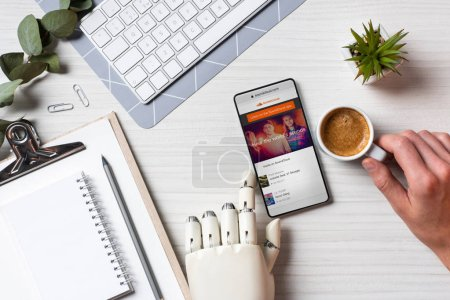Photo for Cropped image of businessman with prosthesis arm using smartphone with soundcloud on screen at table with coffee cup in office - Royalty Free Image