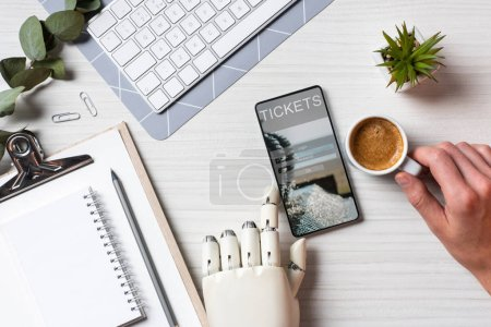 Photo for Partial view of businessman with prosthesis arm using smartphone with tickets on screen at table with coffee cup in office - Royalty Free Image