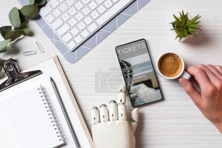 Photo pour Vue partielle de l'homme d'affaires avec bras de prothèse à l'aide de smartphone avec des billets à l'écran au tableau avec une tasse de café au bureau - image libre de droit