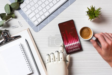 Photo for Cropped image of businessman with prosthesis arm using smartphone with trading courses on screen at table with coffee cup in office - Royalty Free Image