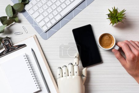 Photo for Partial view of businessman with prosthesis arm using smartphone with blank screen at table with coffee cup in office - Royalty Free Image