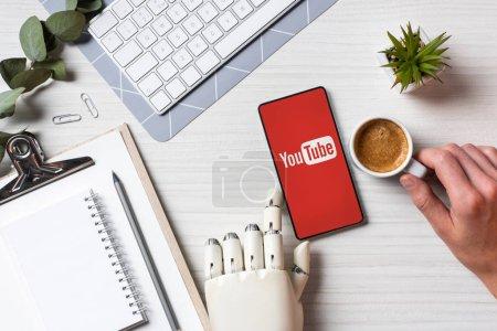 Photo pour Cropped image d'homme d'affaires avec bras de prothèse à l'aide de smartphone avec youtube sur écran à table avec une tasse de café au bureau - image libre de droit