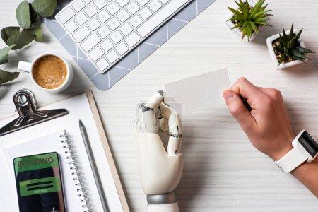Photo pour Image recadrée de l'homme d'affaires avec la main de cyborg et smartwatch tenant la carte de visite vierge à table avec smartphone réservable sur écran au bureau - image libre de droit