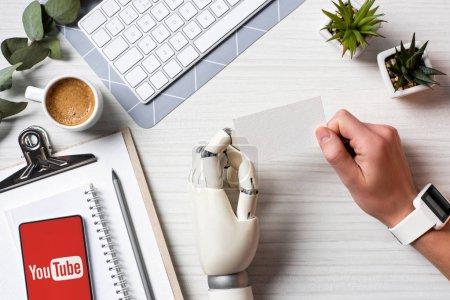 Photo pour Vue partielle de l'homme d'affaires avec la main de cyborg et smartwatch tenant la carte de visite vierge à table avec smartphone avec youtube sur écran au bureau - image libre de droit