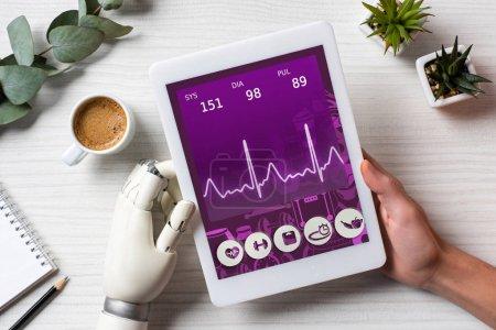 Foto de Recortar imagen de empresario con mano, cyborg con tableta digital con aplicación médica en pantalla a la mesa con la taza de café en la oficina - Imagen libre de derechos