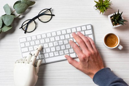 Photo for Cropped image of business with prosthesis hand typing on computer keyboard at table in office - Royalty Free Image